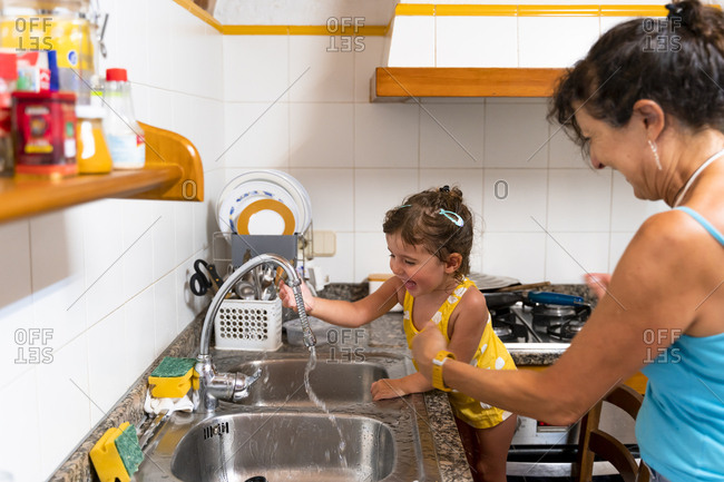 Little girl and grandmother playing with water in the kitchen