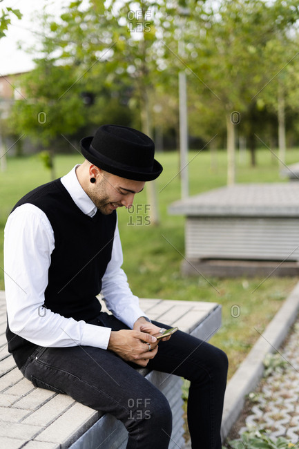 Stylish man sitting on bench outdoors looking at cell phone