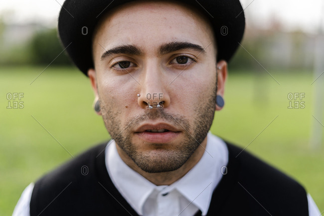 Portrait of young man with nose piercing and earrings