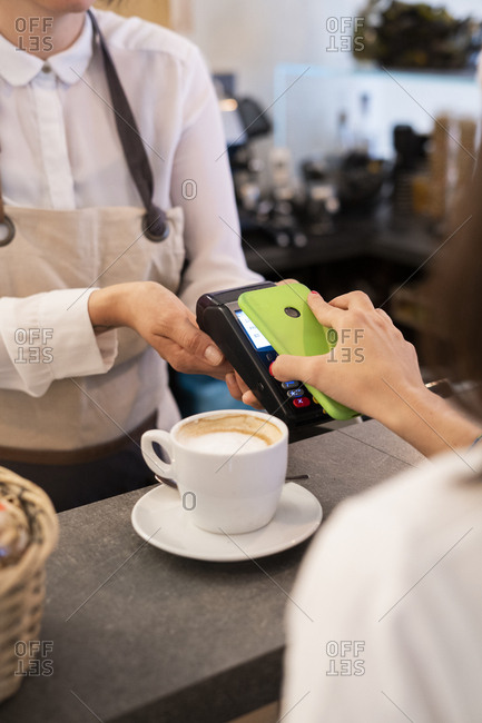 Close-up of customer paying cashless with smartphone in a cafe