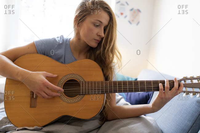 Young woman at home playing guitar with damaged string