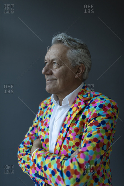 Senior businessman wearing colorful sports jacket looking away