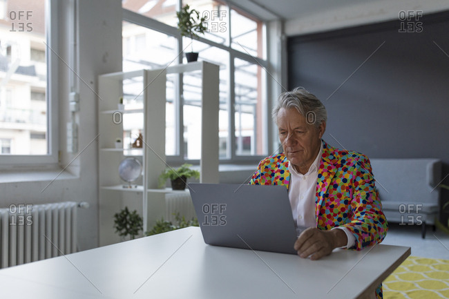 Senior businessman wearing colorful sports jacket using laptop