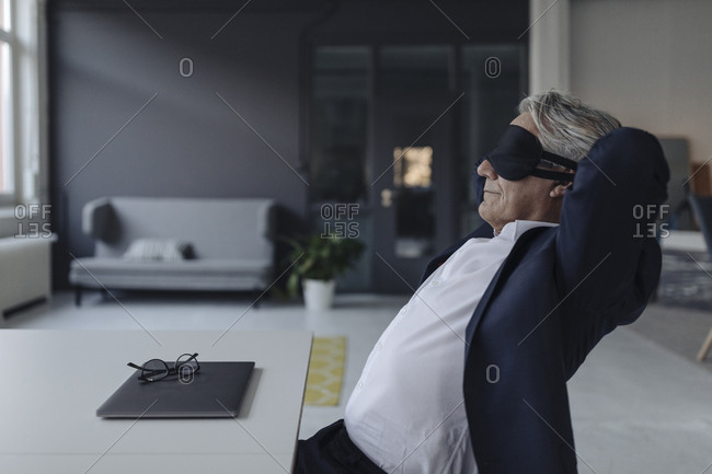Senior businessman wearing eye mask at desk