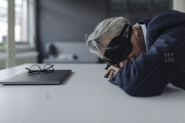 Senior businessman wearing eye mask lying on desk