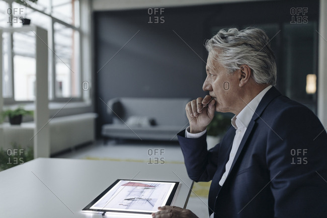 Senior businessman using tablet with architectural plan