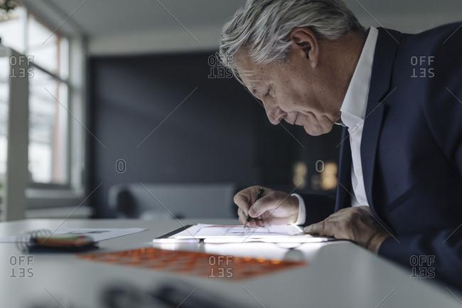 Senior businessman drawing on shining tablet