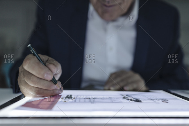 Close-up of senior businessman drawing on shining tablet