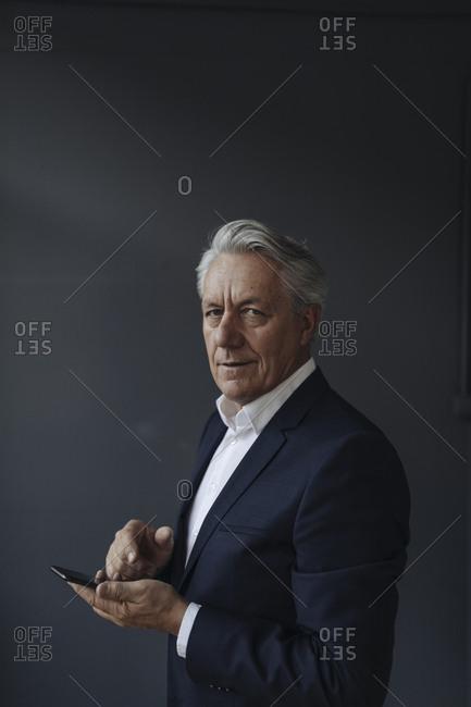 Portrait of a senior businessman holding cell phone