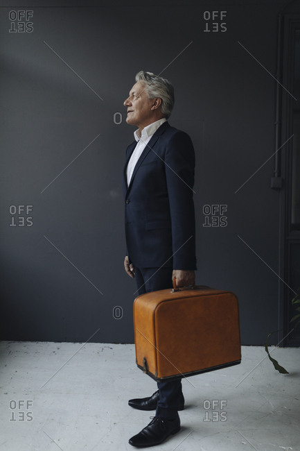 Senior businessman holding old-fashioned suitcase