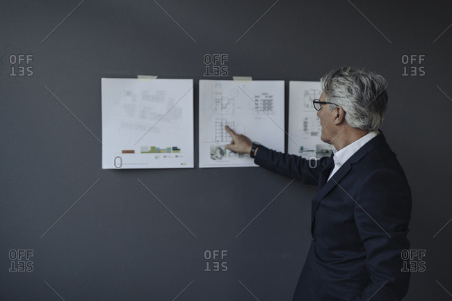 Senior businessman looking at papers hanging on the wall