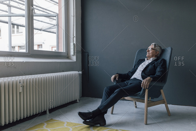 Senior businessman sitting in armchair looking out of the window