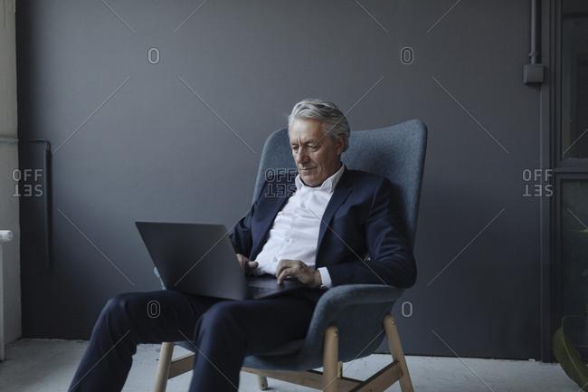 Senior businessman sitting in armchair using laptop