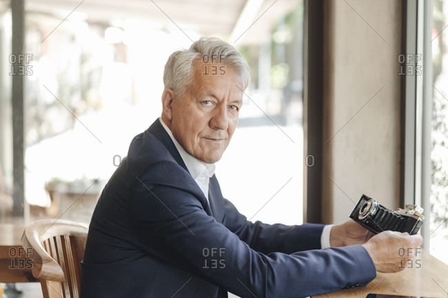 Portrait of senior businessman holding old-fashioned camera in a cafe