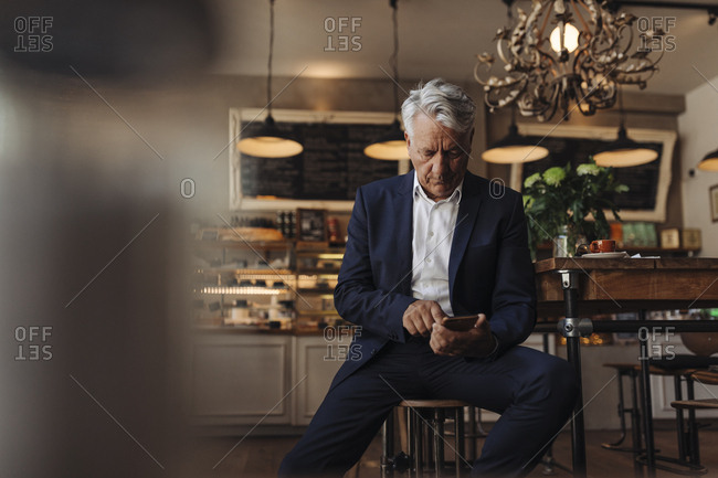 Senior businessman using cell phone in a cafe
