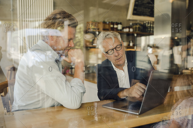 Two businessmen with laptop meeting in a cafe