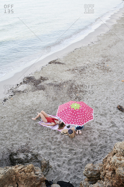 Young woman lying on towel at the beach sunbathing