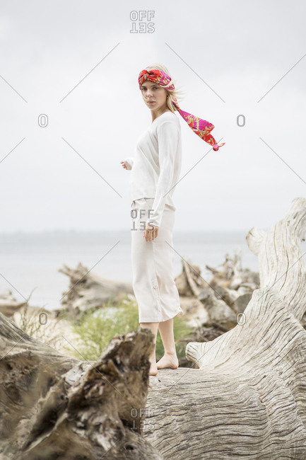 Young woman with hair-band standing on dead tree at the beach