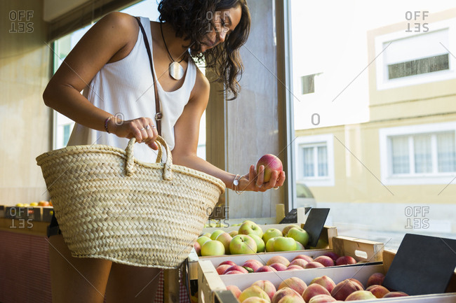 Young woman in organic store choosing apples