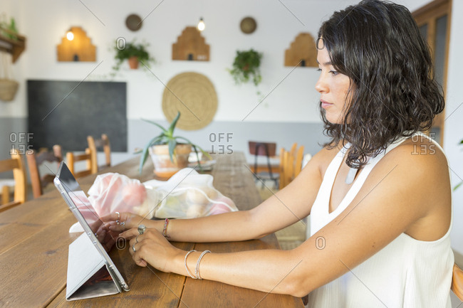 Young woman in organic store- using tablet