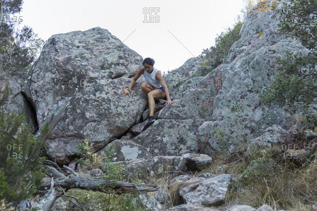 Young Asian woman climbing in a rock wall