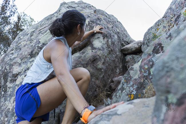 Young Asian woman climbing on a rock