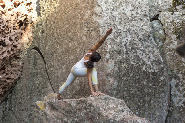 Young Asian woman practicing yoga on a rock- triangle pose