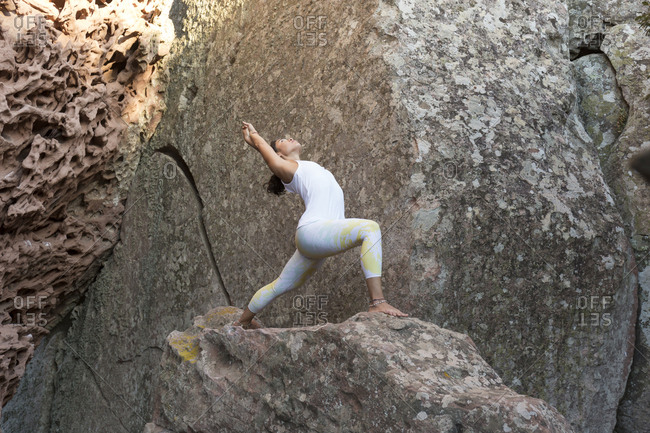 Young Asian woman practicing yoga on a rock- warrior pose