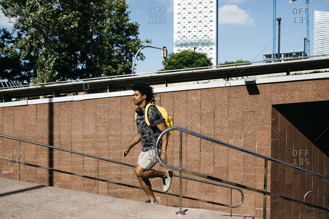Man with yellow backpack and headphones running upstairs- Barcelona- Spain