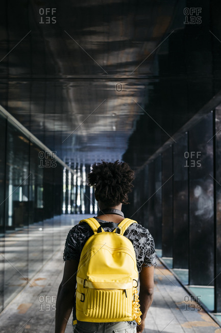 Back view of man with yellow backpack walking through a passage- Barcelona- Spain