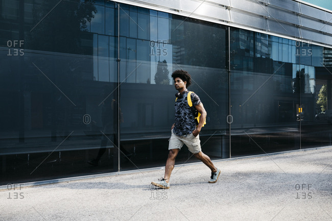 Man with yellow backpack and headphones walking down the street- Barcelona- Spain