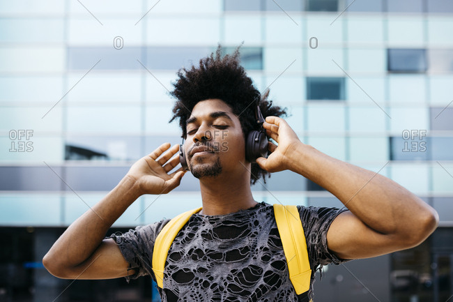Portrait of man listening music with cordless headphones- Barcelona- Spain