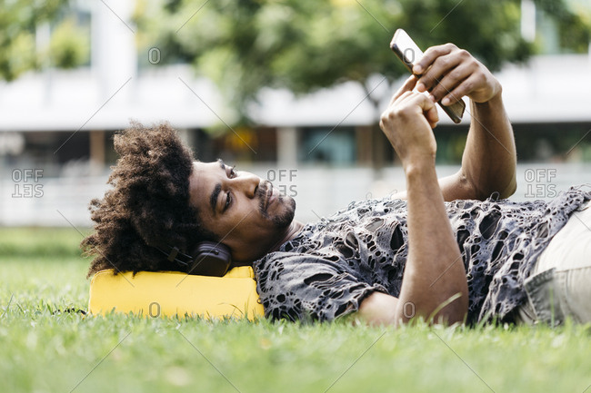 Man lying on a meadow listening music with headphones while using mobile phone- Barcelona- Spain