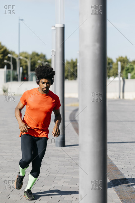 Young man jogging in the city- listening to music