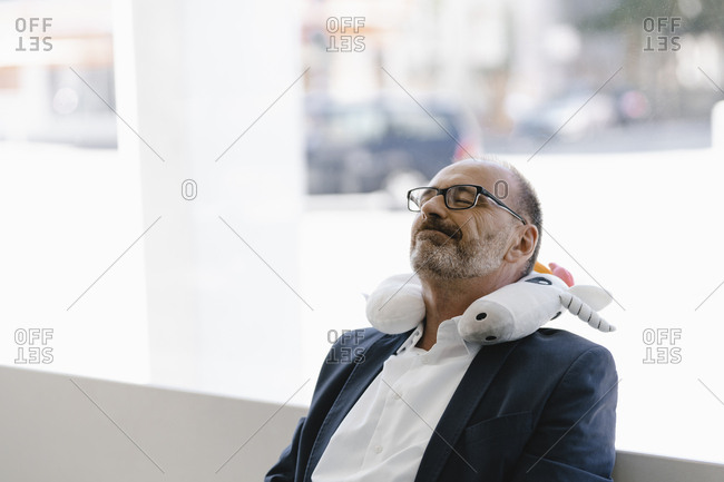 Businessman taking a nap- with a unicorn pillow around his neck