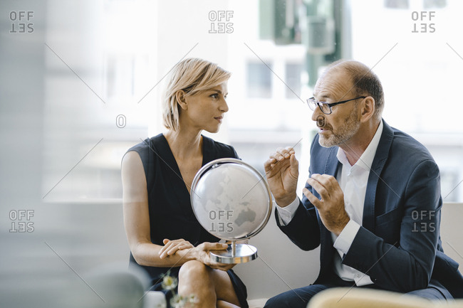Businessman and woman sitting in coffee shop- looking at globe- discussing business