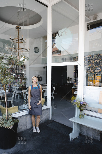 Woman with apron standing in front of coffee shop-