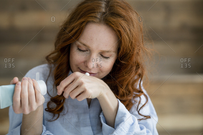 Portrait of redheaded woman smelling cream