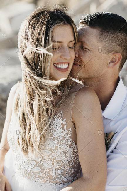 Happy affectionate bride and groom hugging outdoors
