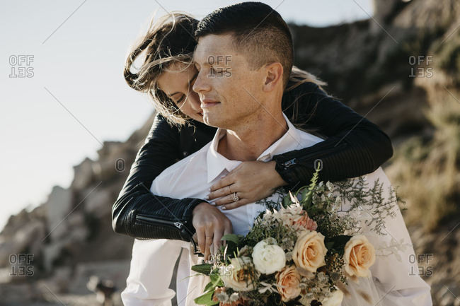 Affectionate bride embracing groom at the coast