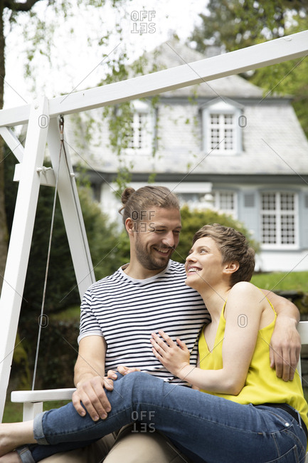 Happy relaxed couple in garden of their home