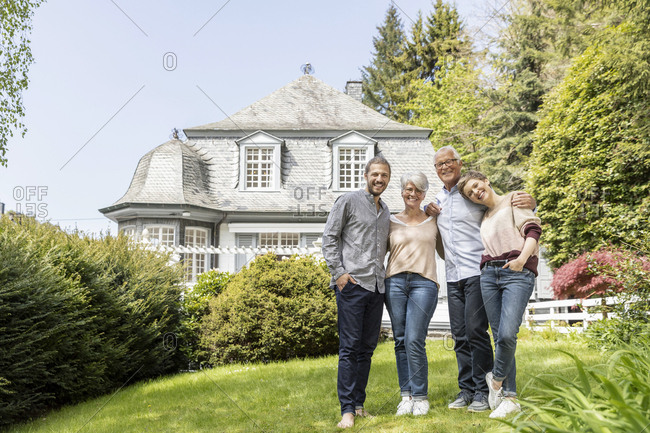 Happy senior couple with adult children standing in garden of their home