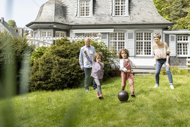 Happy extended family playing football in garden