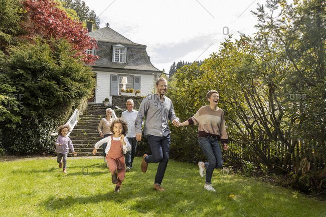 Happy extended family running in garden of their home