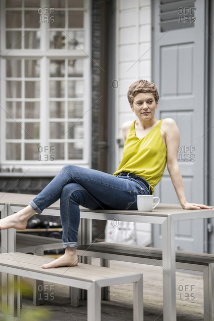 Woman with cup of coffee sitting on terrace table