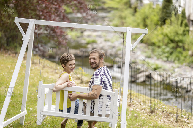 Portrait of smiling couple sitting on canopy swing in garden