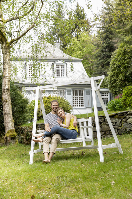 Happy couple relaxing in garden of their home