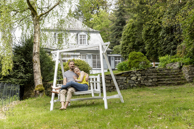 Relaxed couple in garden of their home