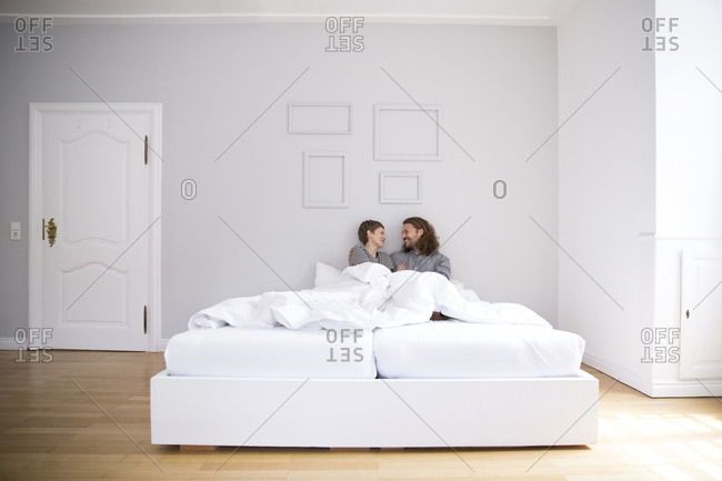 Happy young couple in bed at home