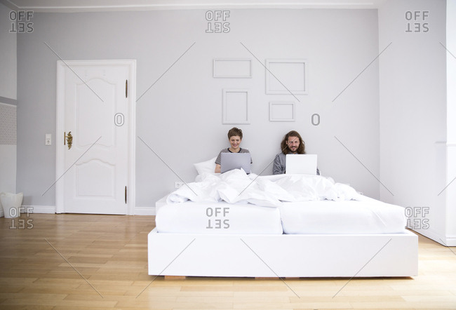 Young couple using laptops in bed at home